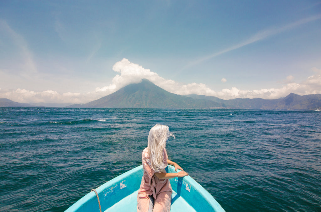 Hiptipico founder Alyssa looks over the helm of a blue boat on vast Lake Atitlan in flowy pink cardigan and light-washed jeans, ethical travel, lake atitlan destinations, where to go on Lake Atitlan, best swimming in lake atitlan