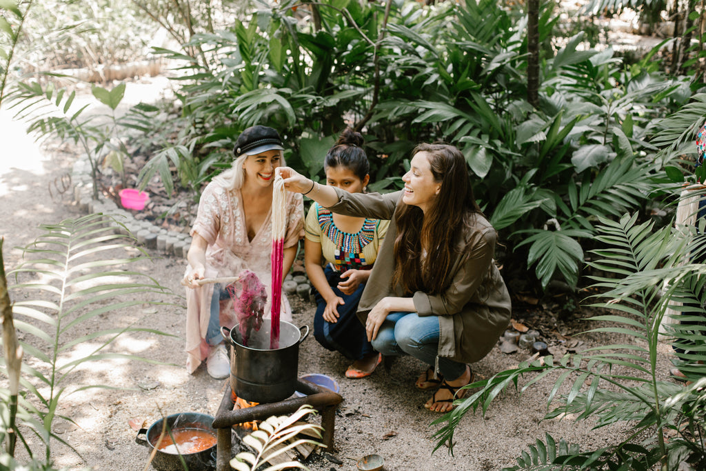 Alyssa and Carina laugh with artisan partner as the fabric is pulled out from the pot as a vibrant pink, natural dyeing workshops, where to learn to weave in Lake Atitlan, what to do in Guatemala, must visit Guatemala