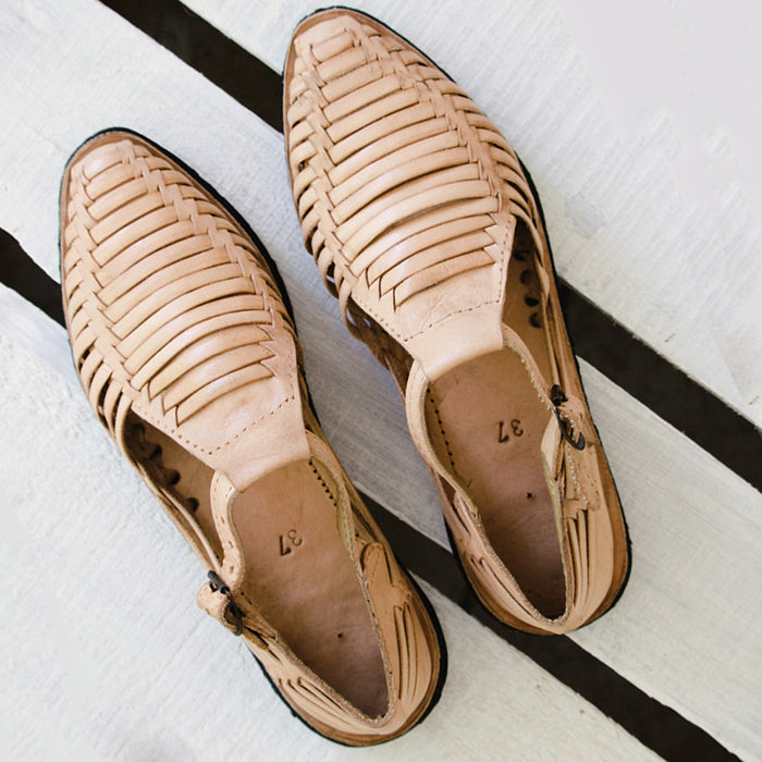 Leather sandals with pointed toes on wood floor. Looking for a pair of vegan leather shoes? Hiptipico offers sneakers, sandals, huaraches, and more in eco-friendly materials.