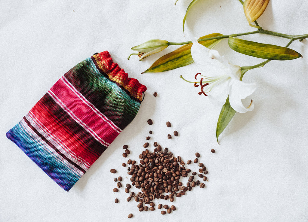 Hiptipico Flatlay with beans, leaves, and woven bag on marble surface, Hiptipico Fair Trade Coffee, Cafe Loco Panajachel Coffee, Buy Fair Trade Coffee Online, Coffee Lover Gift Idea, Purchase Guatemalan Huehuetenango Coffee