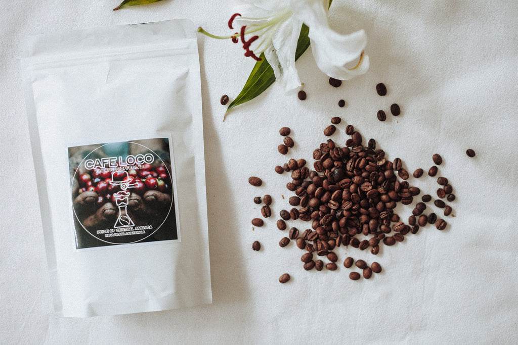 Coffee packaging with beans and leaves on a marble surface, Hiptipico coffee, Cafe Loco coffee in panajachel, ethically sourced coffee beans.