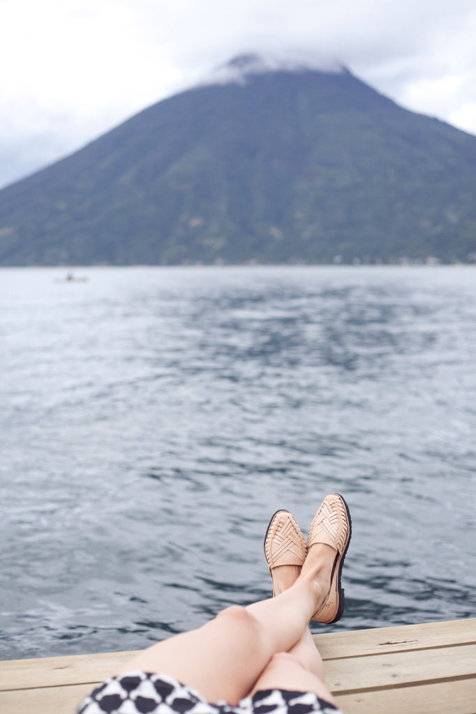 Model wearing pointed leather sandals over view of Lake Atitlan and a volcano, ethically made fashion options for boho travelers, artisan crafted leather sandals from Guatemala