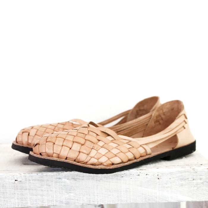 Artisan-made leather flats on cement surface against white background.Looking for a pair of vegan leather shoes? Hiptipico offers sneakers, sandals, huaraches, and more in eco-friendly materials.