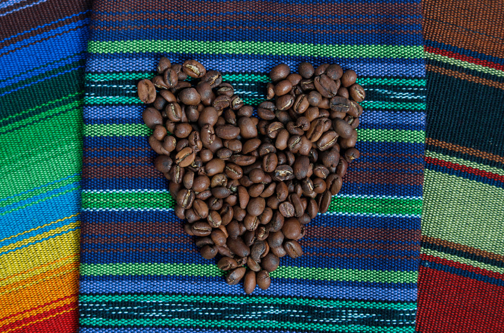 Coffee beans arranged in a heart on guatemalan textile, Hiptipico Fair Trade Coffee, Cafe Loco Panajachel Coffee, Buy Fair Trade Coffee Online, Coffee Lover Gift Idea, Purchase Guatemalan Huehuetenango Coffee
