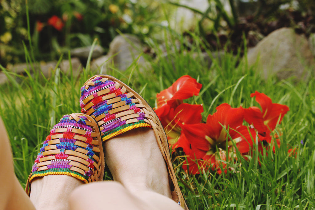 hiptipico santander flats in field with red flowers complimenting the reds and purples of the weaving, handmade bohemian huarache, urban outfitters sandals, handmade huaraches, multicolor shoes, summer sandals