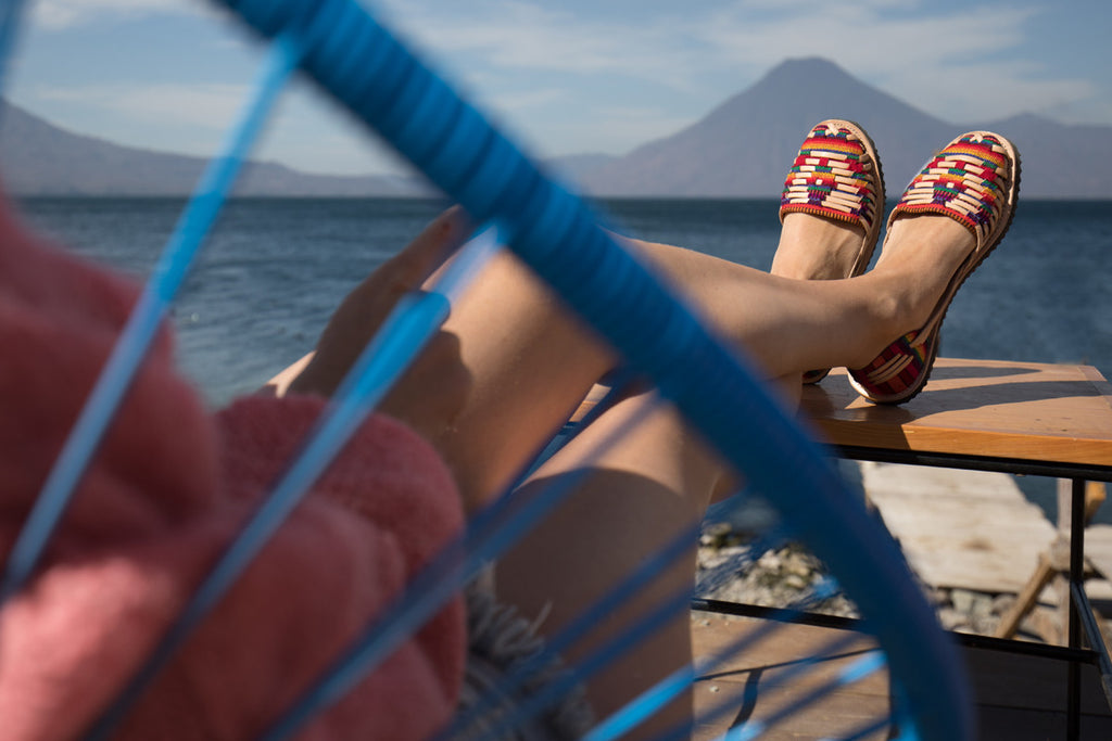 Model in blue chair with feet up overlooking Lake Atitlan on a clear day, Hiptipico Handcrafted Leather Flats, Boho Braided Leather Huaraches, Bohemian Sandals, Colorful textile woven tapestry gladiator sandals, Boho Braided Sandals in Vegan Leather, Vegan Options for Guatemalan Shoes