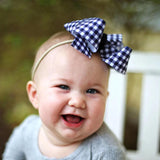 Baby bow headband in navy and white plaid checks on nude nylon band