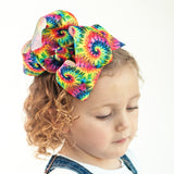 Big bright hair bow with rainbow tie-dye print in primary colors