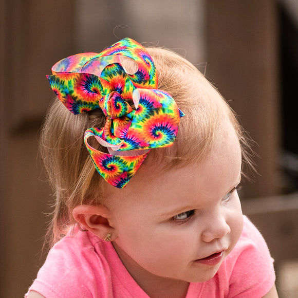 Brightly colored boutique bow with rainbow tie-dye print for baby girl