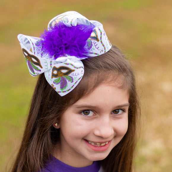 Big white Mardi Gras hair bow with purple feathers, masks, and fleur-de-lis accents in gold and glitter