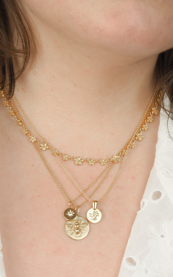 layering coin necklace with flower design