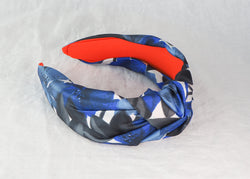 A blue and black abstract floral print wide knotted headband made from vintage deadstock fabric