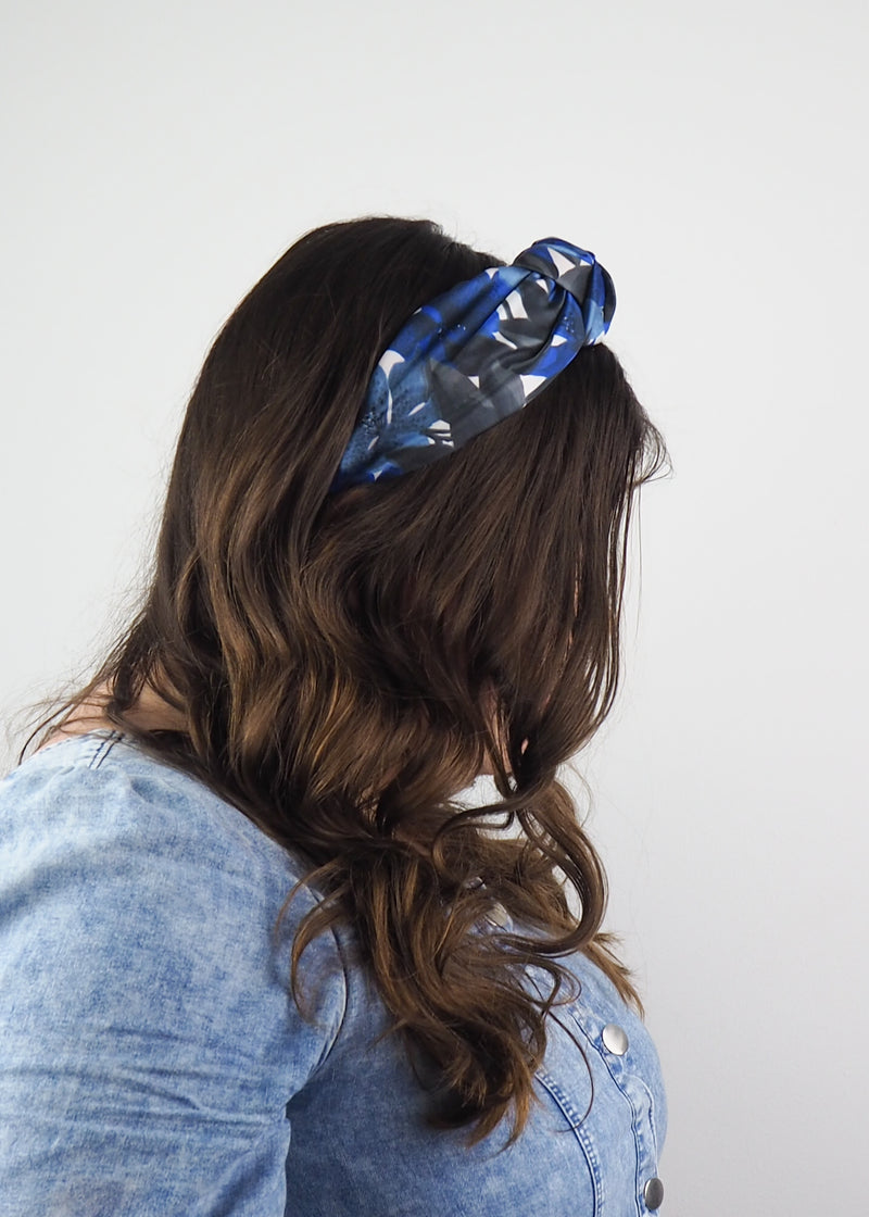 A blue and black wide knotted headband madxe from vintage deadstock fabric with an abstract floral print
