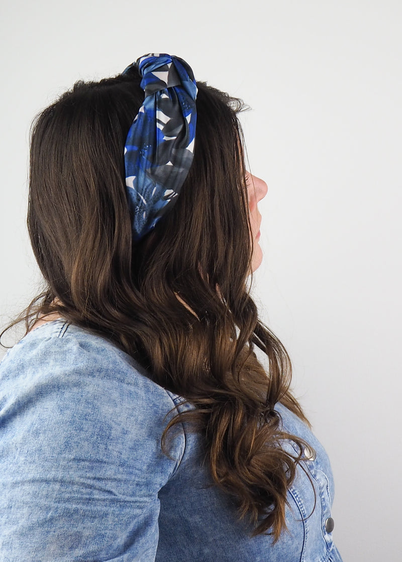 A wide knotted headband with an abstract blue and black floarl print made from deadstock vintage fabric