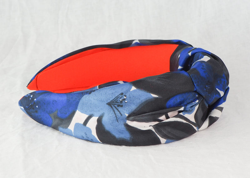 a wide knotted headband with blue and black floral print made from vintage deadstock satin fabric