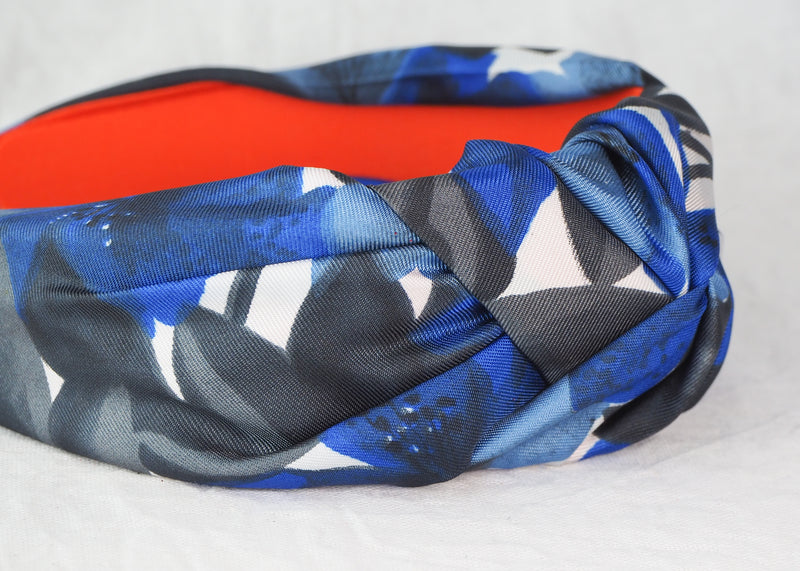 close up of a wide knotted headband with a blue and black floral print made from vintage fabric