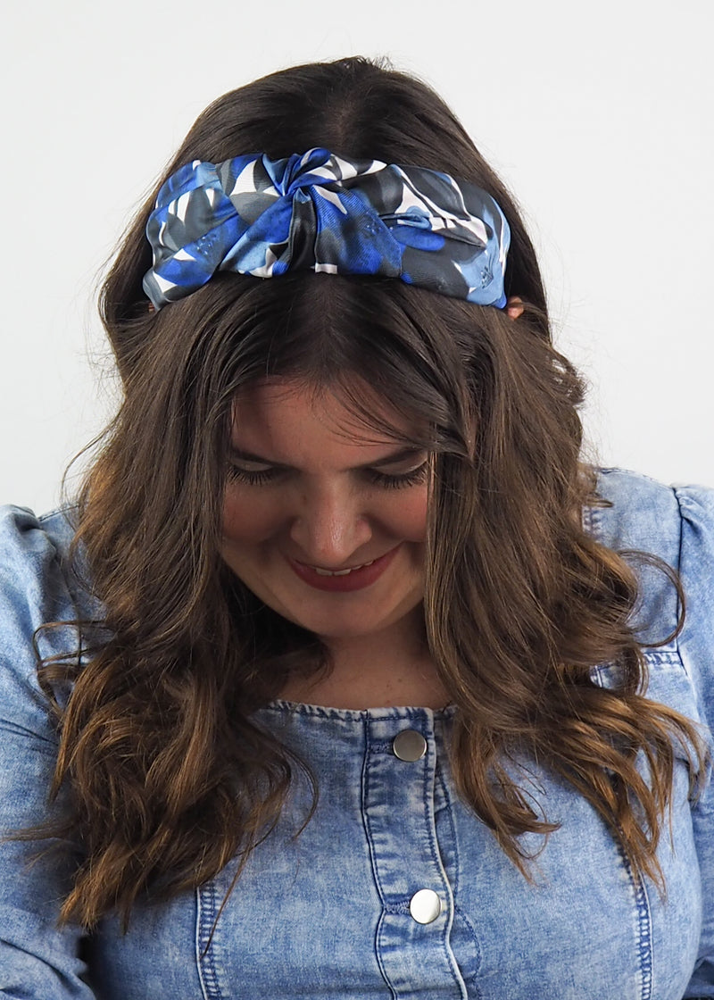 A black, blue and white wide knotted floral headband with an abstract floral print made from vintage fabric
