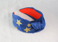 a blue velvet wide knotted headband with printed gold glitter stars handmade in Birmingham