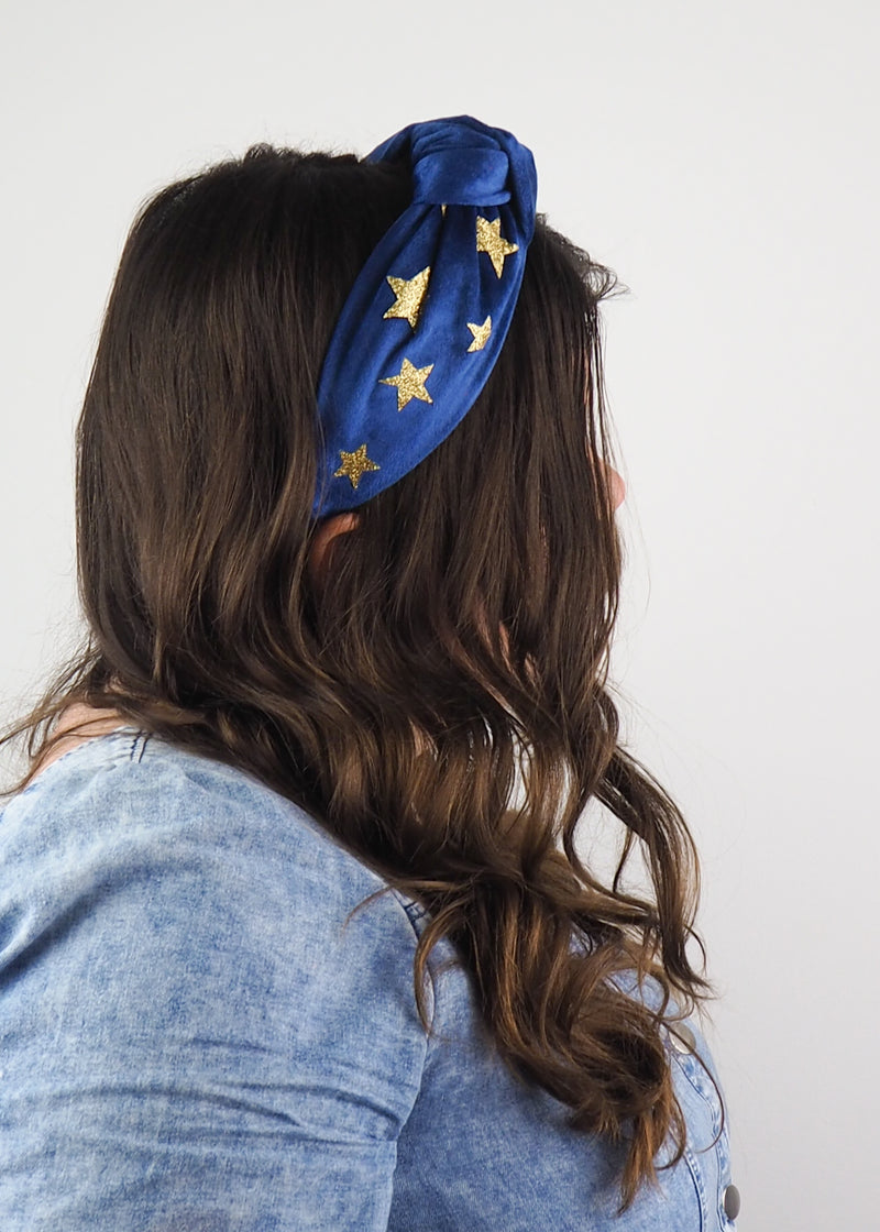 a blue velvet wide knot headband printed with gold glitter stars