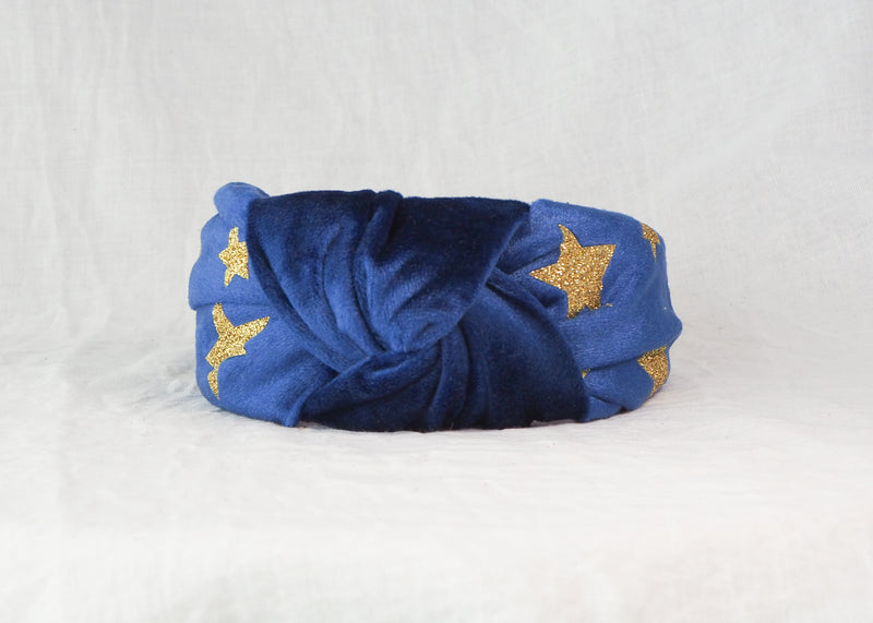 A blue velvet wide knotted headband with gold glitter stars