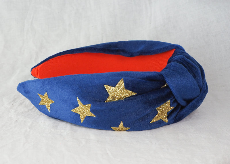 a blue velvet headband with gold glitter stars