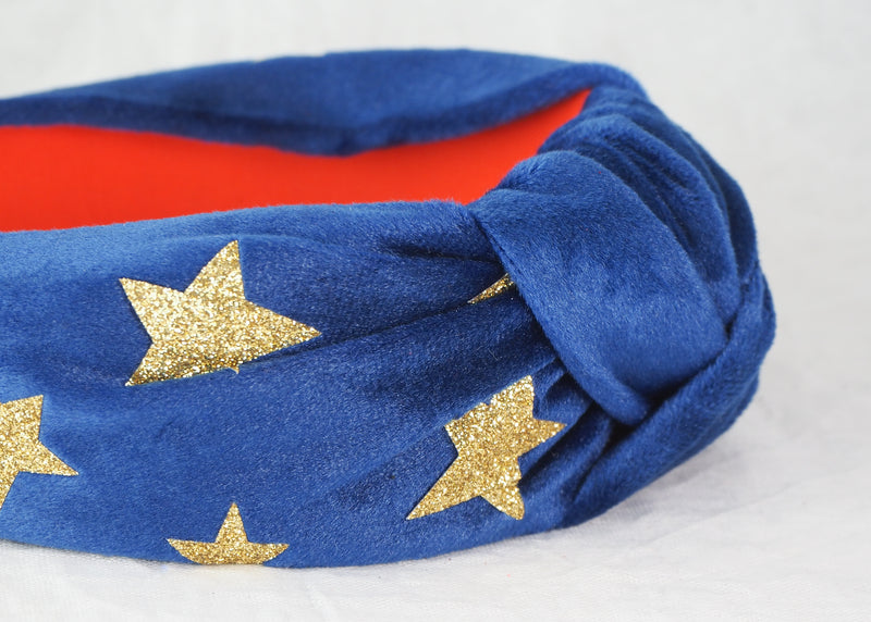 a wide knot headband made from blue velvet fabric with gold glitter stars