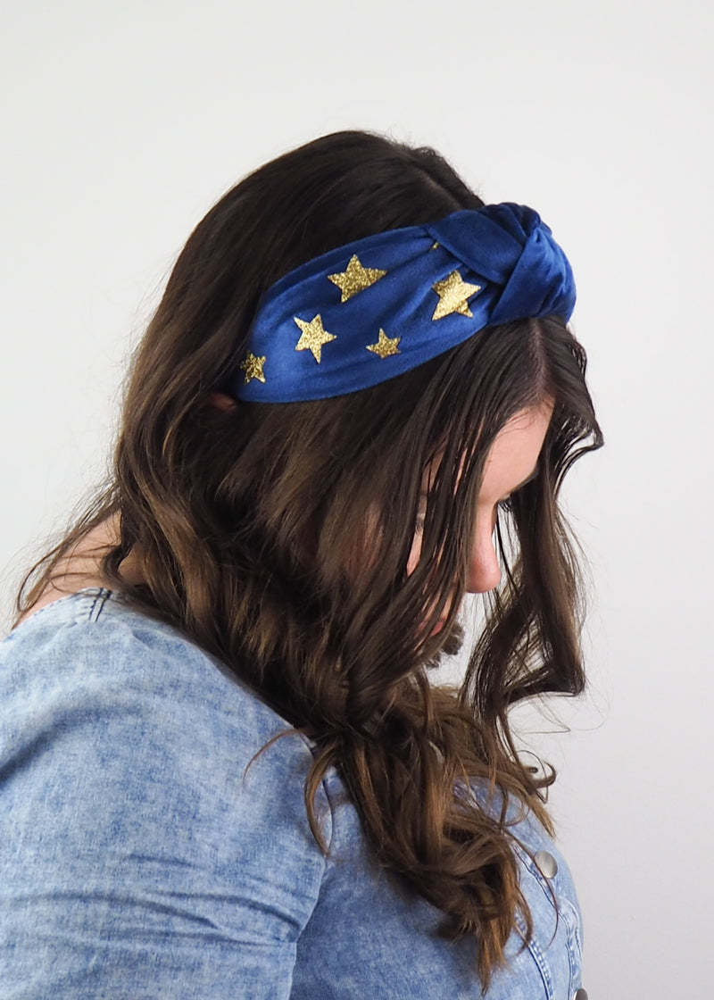 a blue wide knotted headband made from velvet fabric and gold glitter stars