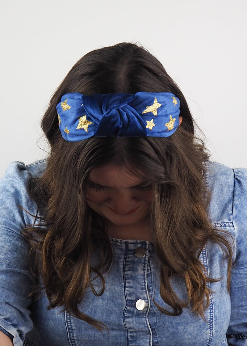 a blue velvet wide knotted headband with gold glitter printed stars