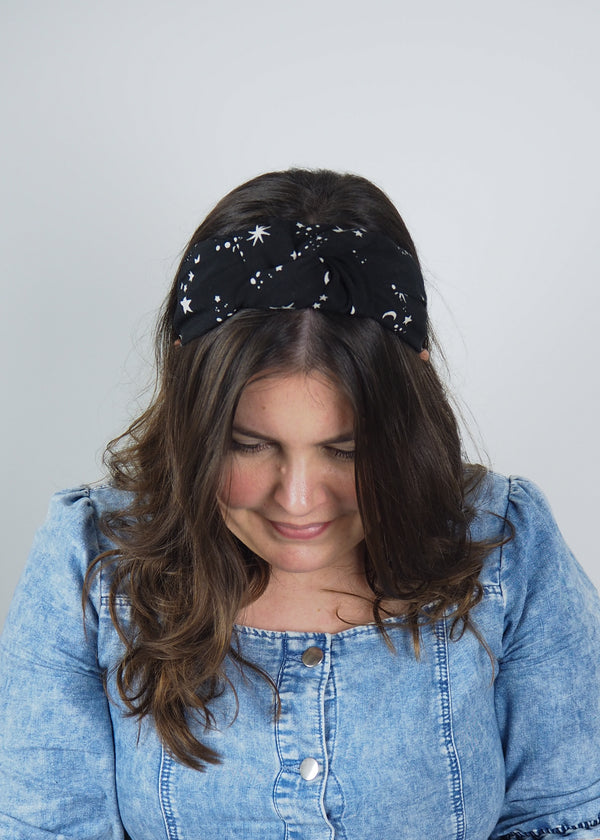 a celestial star print wide knotted headband with white stars printed on a black background