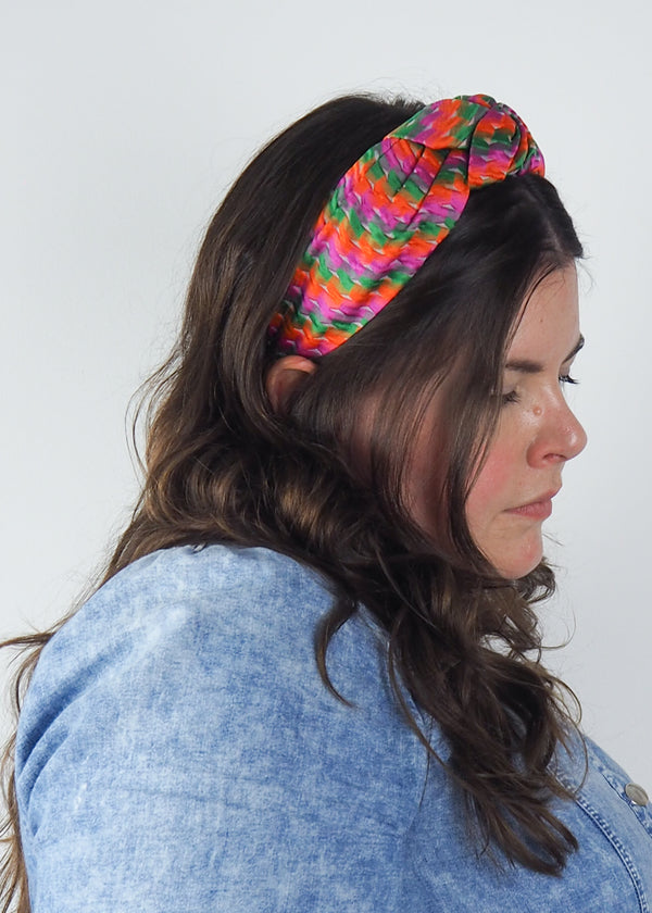 a colourful jacquard wide knotted headband made from orange, green and pink fabric. Handmade in Bimringham