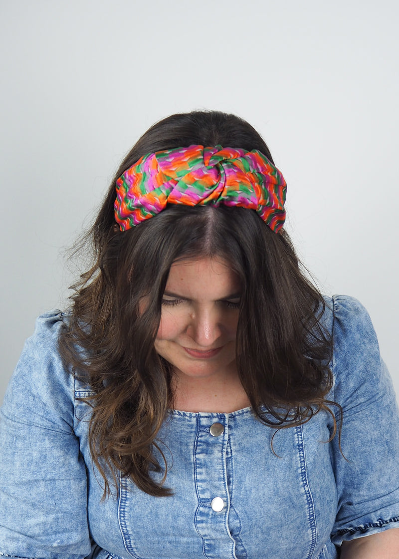 a wide knotted headband made from colourful orange, green and pink woven jacquard fabric