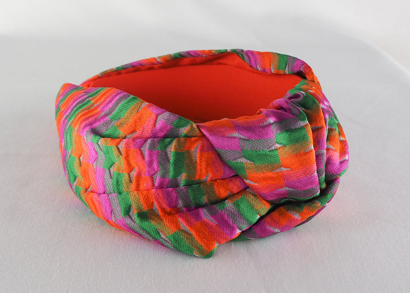 a colourful wide knot headband made from orange, green and pink jacquard fabric handmade in Birmingham