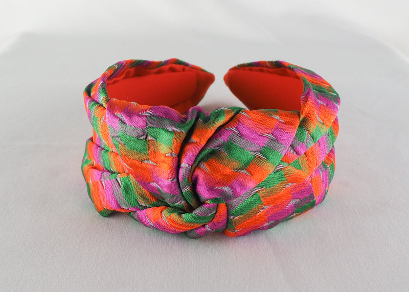 a colourful wide knotted headband made from orange, green and pink jacquard fabric in Birmingham