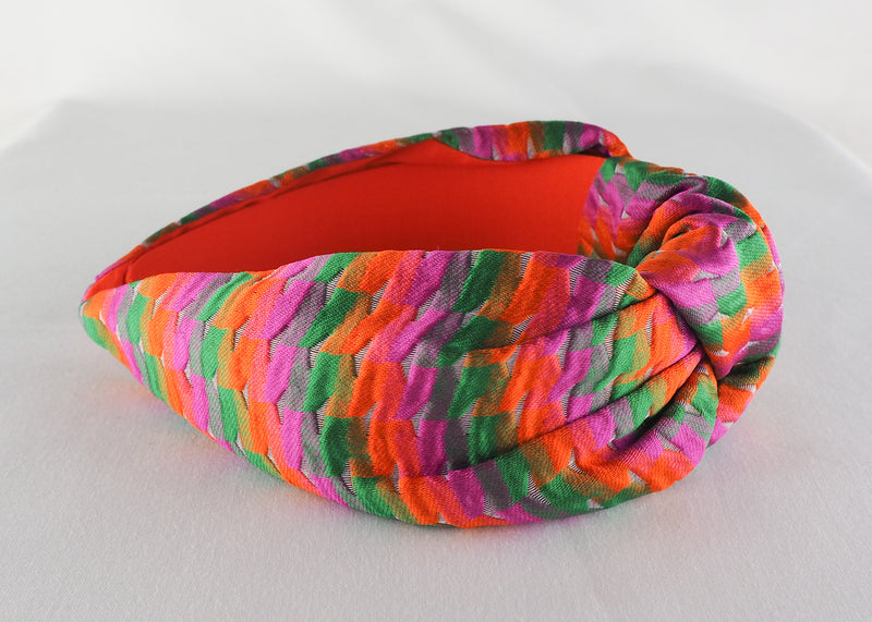 a wide knotted headband made from pink, green and orange woven jacquard fabric handmade in bormingham