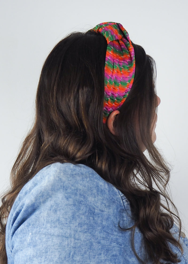 a wide knotted headband handmade in Birmingham from orange, green and pink woven jacquard fabric
