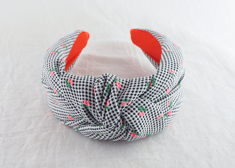 a wide knotted headband with black and white polka dots and tiny pink flowers