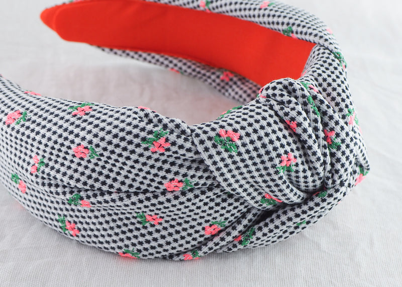 a black and white spotted headband with fluorescent pink tiny flowers