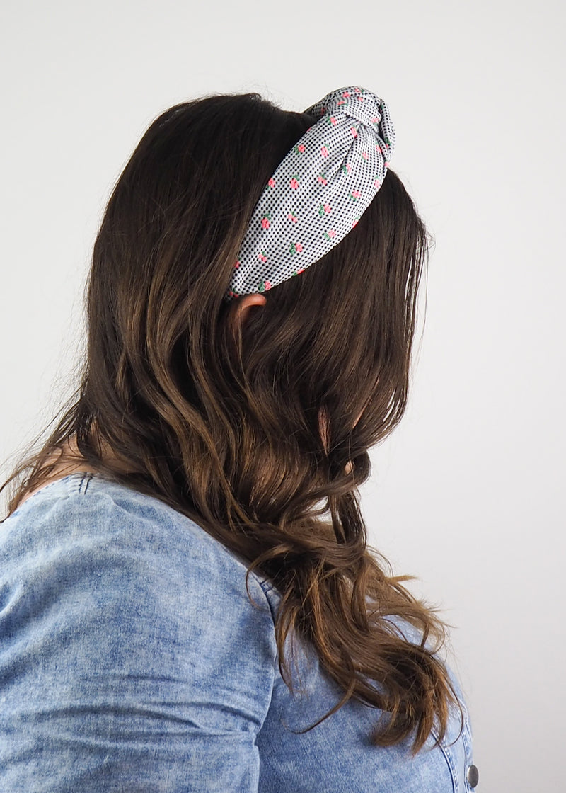 a wide knotted headband made from black and white fabric with tiny pink flowers