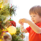 young boy decorating tree