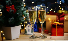 An image of two champagne glasses with a Christmas tree and presents in the background.
