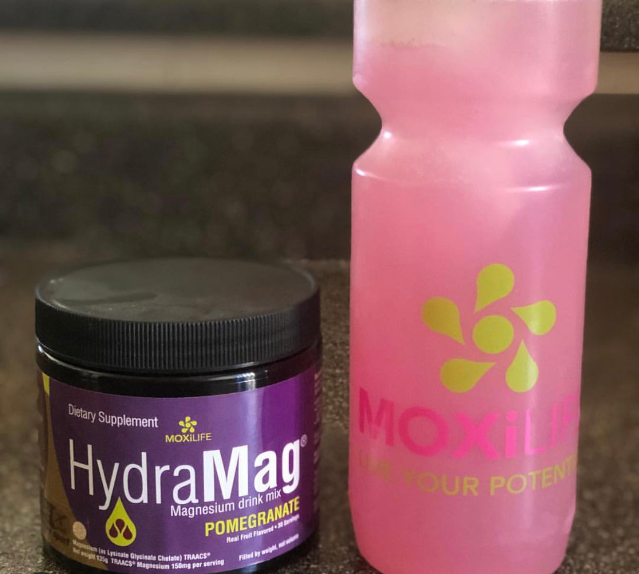 Hydramag 30 svg Canister sitting next to Moxilife water bottle with pink pomegranate hydramag inside