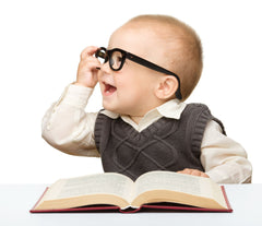 Little boy wearing glasses and reading a book