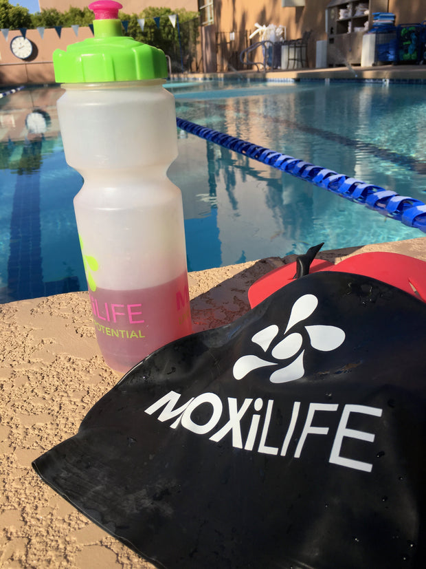 MOXiLIFE water bottle and swim cap by the pool