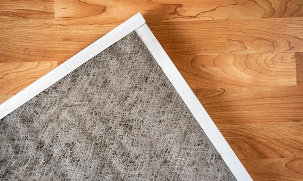 An air filter laid out carefully on a wooden floor.