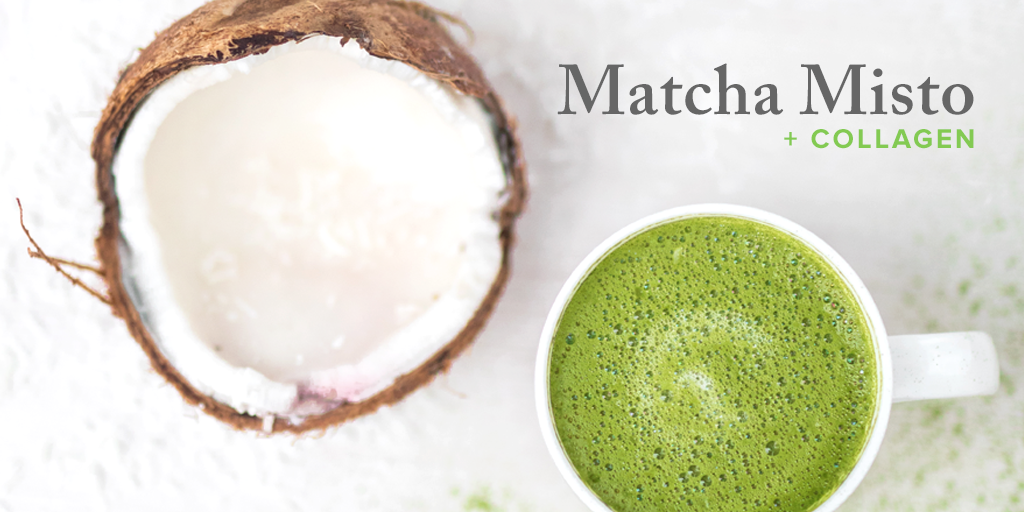 Image showing a cracked open coconut and a mug filled with emerald green matcha. Matcha powder is sprinkled around the mug of matcha.