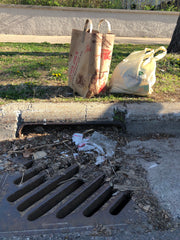 Bags of trash collected and a clean drain
