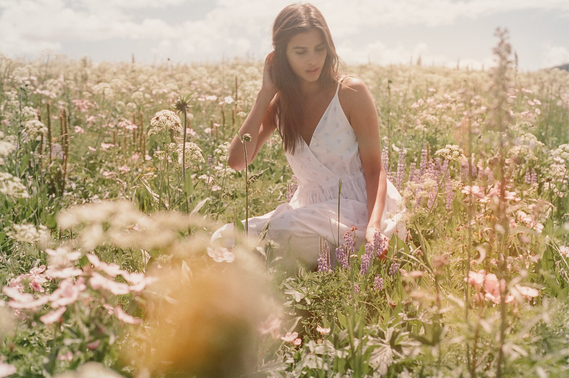 We're inspired daily by the beauty of Mother Earth. Karina sits in a field of wildflowers in Wyoming.