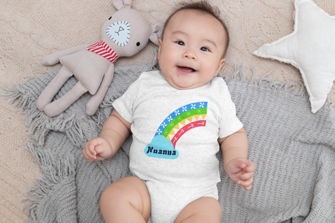 baby layin on blanket wearing a white onesie with a rainbow and word Nuanua on it