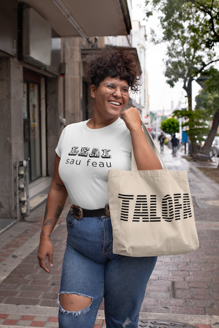Woman holding canvas tote bag with word Talofa on it
