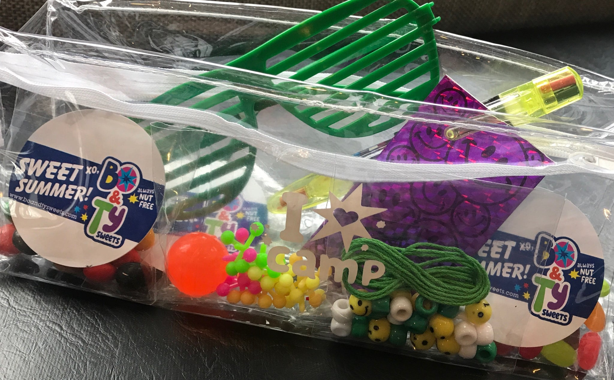 Camp bunk gift filled with nut free and peanut free candy and other bunk junk including set of jacks, sunglasses, camp string and beads, notepad and pencil